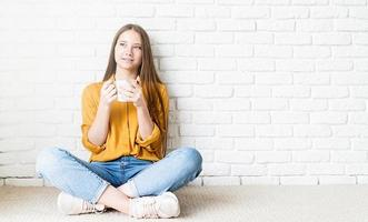Attractive teenager woman in yellow shirt drinking tea sitting on the floor photo
