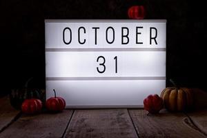October 31 light box in the dark room with pumpkins on wooden floor photo