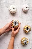 Woman hands with black nails holding colored golden pumpkin photo