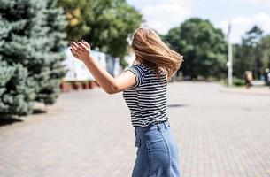 young pretty caucasian woman in casual clothes having fun turning around on urban park background in the park photo