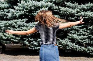 young pretty caucasian woman in casual clothes having fun turning around on fir trees background in the park photo