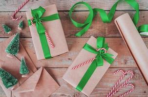 christmas gifts wrapped in craft paper with green ribbon top view flat lay on wooden background photo