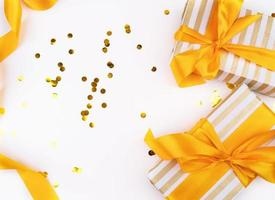 Christmas gifts wrapped with gold and white paper, confetti and a golden ribbon top view flat lay photo