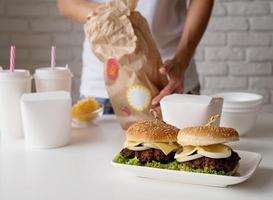 Mujer en ropa de casa desembalaje de comida a domicilio con hamburguesas, cajas de fideos y bebidas foto