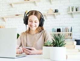 Sonriente jovencita en auriculares charlando con su smartphone mientras hace su homewotk foto