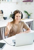 Sonriente jovencita sentada en el escritorio en la cocina aprendiendo usando su computadora portátil, saludando hola charlando con amigos foto