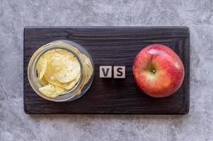 chips versus vista superior de manzana sobre fondo oscuro foto