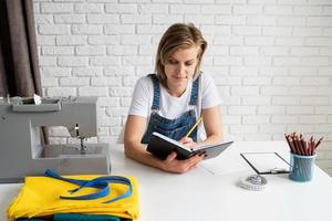 Young blond woman tailor drawing a sketch ready to sew photo