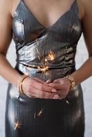 mujer en un vestido de fiesta sosteniendo una bengala en sus manos foto