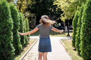 young pretty caucasian woman in casual clothes having fun turning around on trees background in the park photo