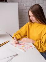 Female artist painting a picture with watercolor in the studio photo