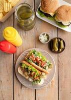 Hot dog with sausage, letuce, cucumber and onion on beigw plate on wooden background photo