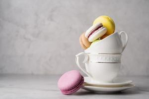 Stack of white coffee cups filled with macaroons on the edge of the table, white brick wall background photo