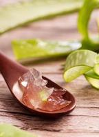 Aloe vera gel with sliced aloe leaves on wooden background photo