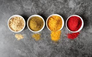 various indian spices in bowls top view on dark concrete background photo