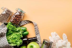 Bolsa ecológica con verduras, semillas de chía, guantes y vista superior de aceite de oliva sobre fondo naranja con espacio de copia foto