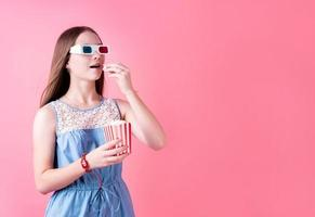 Excited female teenager girl wearing 3D glasses eating popcorn isolated on pink background photo