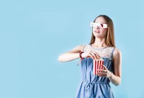 Excited female teenager girl wearing 3D glasses eating popcorn isolated on blue background photo