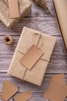 Gift boxes wrapped in craft paper with tags and labels on wooden background top view flat lay photo