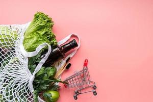 Bolsa de malla ecológica con verduras, cepillos de dientes de madera, guantes y vista superior de aceite de oliva sobre fondo rosa con espacio de copia foto