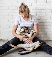 Blond woman holding her dog at home photo