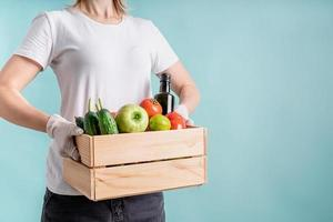 Mujer rubia en guantes sosteniendo una caja de madera llena de verduras con espacio de copia foto
