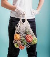 Mujer en guantes sosteniendo mallas mallas con verduras aislado sobre fondo azul. foto