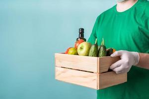 hombre en guantes sosteniendo una caja de madera llena de verduras foto