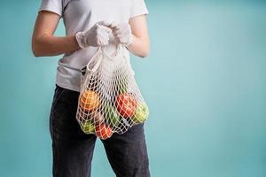 Mujer en guantes sosteniendo mallas mallas con verduras aislado sobre fondo azul con espacio de copia foto