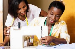 happy seamstresses behind a sewing machine photo