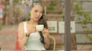 Asian teenage girl holds a coffee cup in a cafe. photo