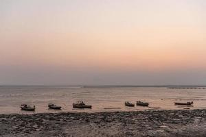 Golden beaches and fishing boats on the beach at dusk photo