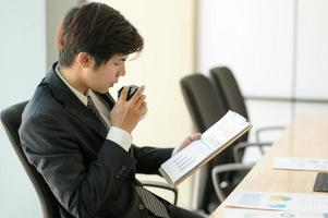 Young executives are checking company earnings. He eats coffee and checks the chart. photo