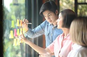 hombres y mujeres jóvenes en la oficina están trabajando juntos. utilizan un bolígrafo y una mano para señalar la nota en el cristal. foto