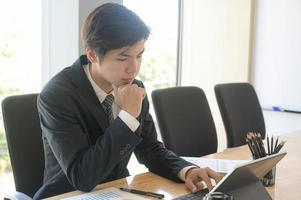 Young executives are checking company earnings. He uses tablet and check the data from chart. photo
