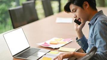 los hombres de negocios jóvenes están llamando para trabajar y usar la computadora portátil. foto