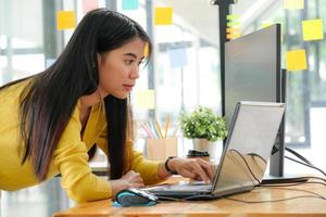 Young Asian female programmer in a yellow shirt stands down to use her laptop and PC in the office. photo