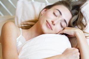 Mujer adolescente durmiendo en la cama en casa, niña durmiendo por la mañana, niña durmiendo en la cama, sin concepto de insomnio foto