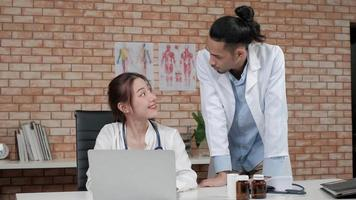 Healthcare team partners. Two young Asian ethnicity doctors in white shirts are coworkers discussing medication in the hospital's clinic office. Specialist persons are experts and professionals. video