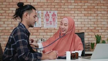 Young beautiful woman doctor is health examining male patient in office of hospital clinic and advising with a smile on medicines. This Asian medical specialist is an Islamic person wearing a hijab. video