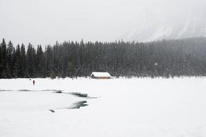 One person dressed in red in a winter landscape. Frozen lake, wooden house and a forest under the snow. Banff National Park, Canada photo