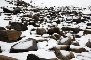 Winter scene. Background with snowed stones close to a frozen river. Canada photo