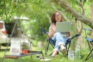 mujer charlando con amigos con una computadora portátil durante el campamento. foto