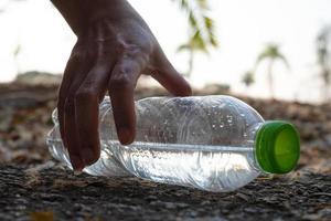Cerrar la mano recogiendo una botella de plástico transparente, beber agua con una tapa verde en la carretera en el parque con un fondo borroso, basura que queda fuera del contenedor foto