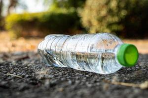 Cerrar una botella de plástico transparente, beber agua con una tapa verde en la carretera en el parque con un fondo borroso, basura que queda fuera de la papelera foto