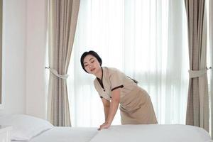Joven y bella sirvienta de Asia arreglando una manta en la cama en la habitación del hotel foto