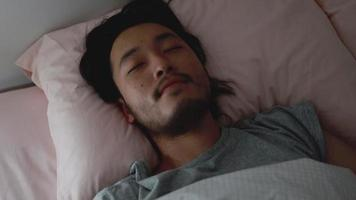 Sleeping Asian man sweet dreaming in the bedroom at home. video
