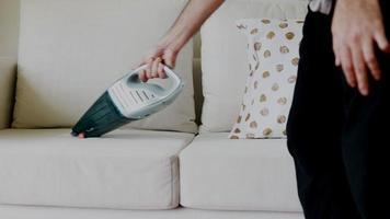 Asian man cleaning sofa with a vacuum cleaner in the living room at home. video