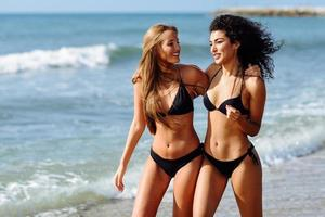 Two young women with beautiful bodies in swimwear on a tropical beach photo
