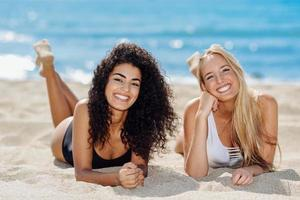 Two young women with beautiful bodies in swimsuit on a tropical beach photo